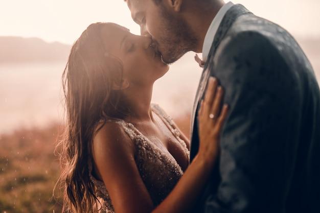 Primo piano della coppia appena sposata in piedi fuori e baciare. momento emotivo nel giorno del loro matrimonio.
