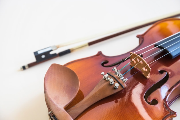 Primo piano della corda del violino con l'arco sul contesto bianco