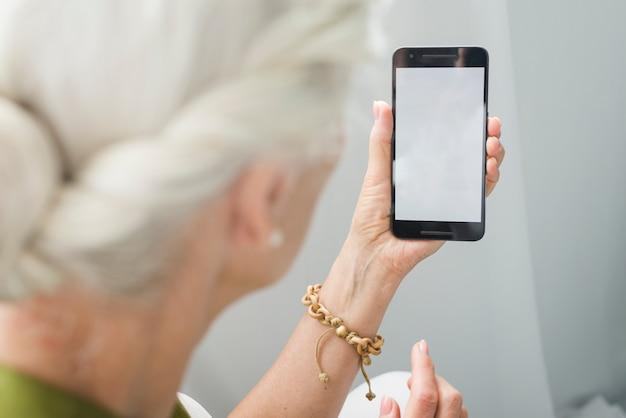 Primo piano della donna anziana che esamina smartphone con lo schermo in bianco