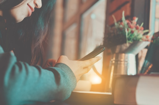 Primo piano della donna asia utilizzando smartphone nel tempo libero con felice.