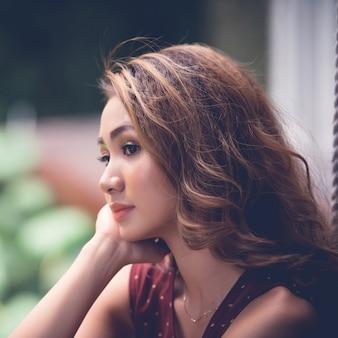 Primo piano della donna asiatica affascinante che fantastica sognando mento sulla sua palma