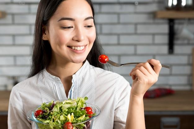 Primo piano della donna asiatica felice che mangia insalata sana