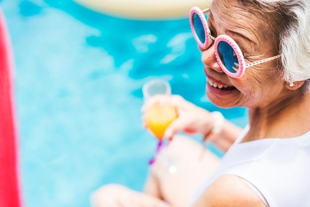 Primo piano della donna asiatica senior con succo in piscina