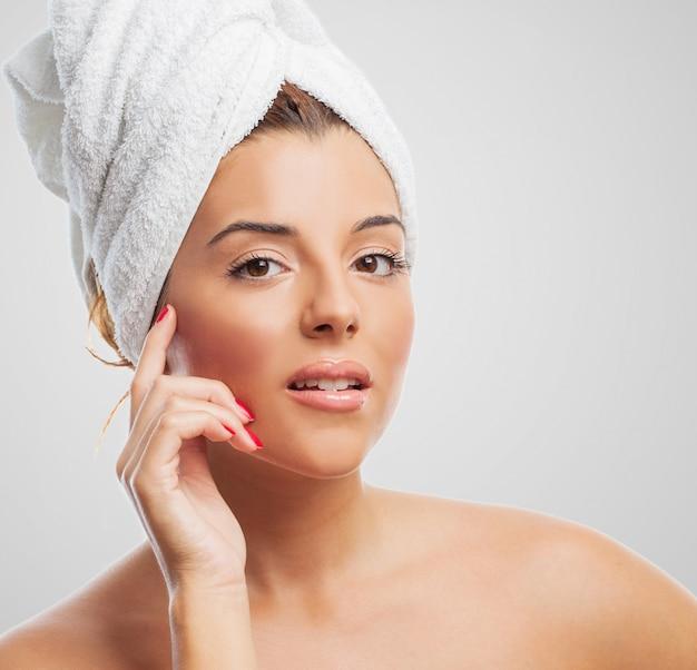 Primo piano della donna attraente in un asciugamano bianco
