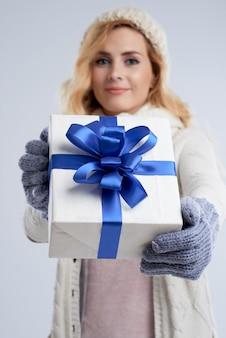 Primo piano della donna bionda che presenta il contenitore di regalo per il natale che lo allunga alla macchina fotografica