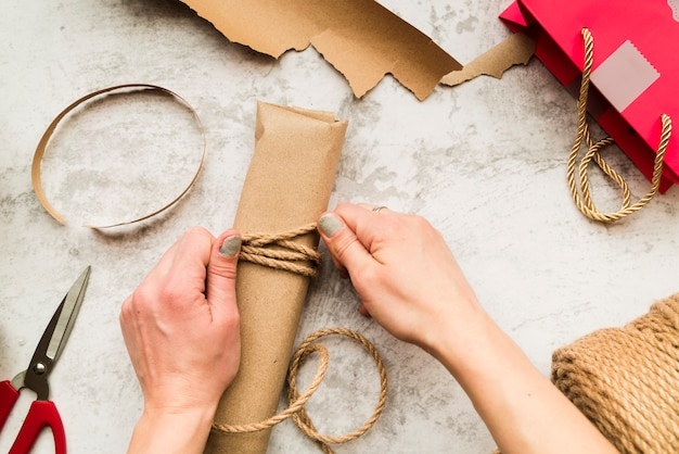 Primo piano della donna che avvolge il contenitore di regalo con corda di iuta sul contesto strutturato