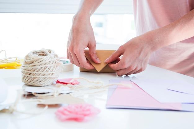 Primo piano della donna che avvolge il contenitore di regalo sulla tavola