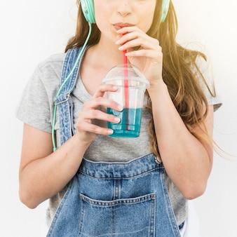 Primo piano della donna che beve cocktail con paglia