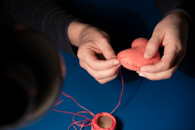 Primo piano della donna che cuce il cuore della peluche