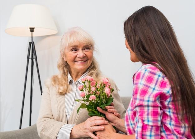 Primo piano della donna che dà il mazzo rosa delle rose del fiore a sua madre senior