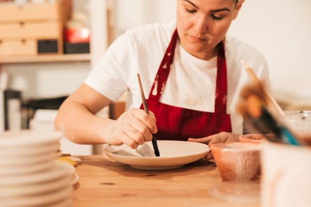 Primo piano della donna che dipinge figura ceramica con il pennello
