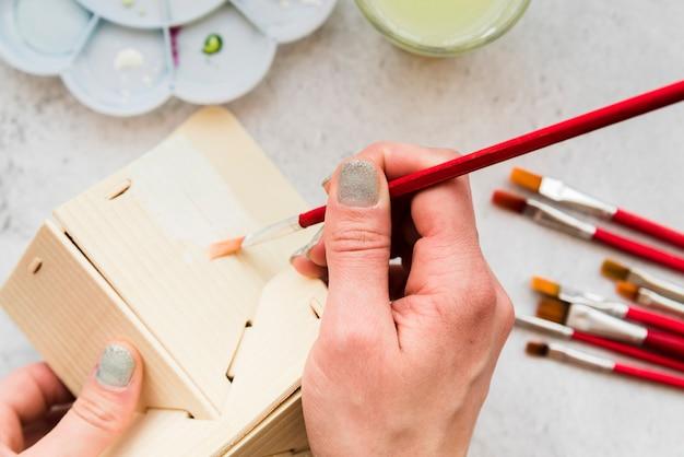 Primo piano della donna che dipinge il modello di casa in legno con pennello