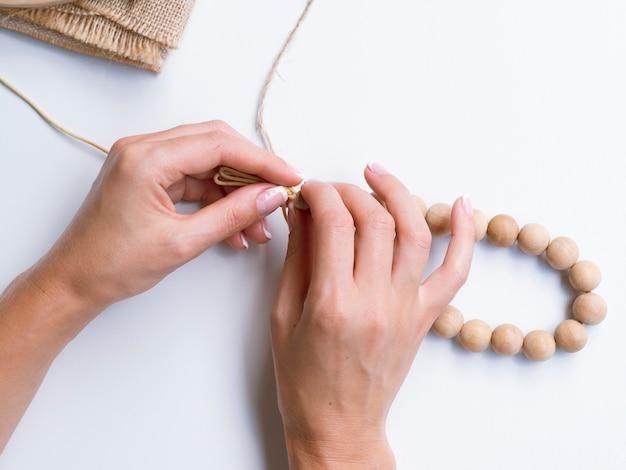 Primo piano della donna che fa gli accessori delle perle di legno