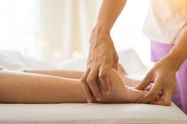 Primo piano della donna che fa massaggio al piede nella spa.