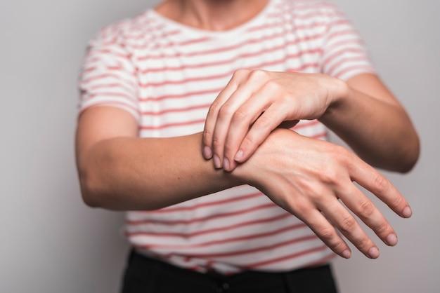 Primo piano della donna che ha dolore al polso che sta contro il fondo grigio