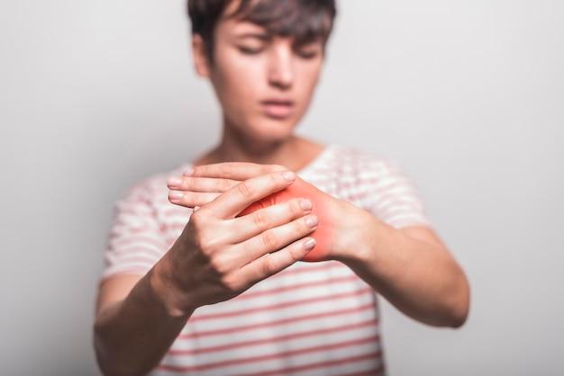 Primo piano della donna che ha dolore della mano contro fondo bianco