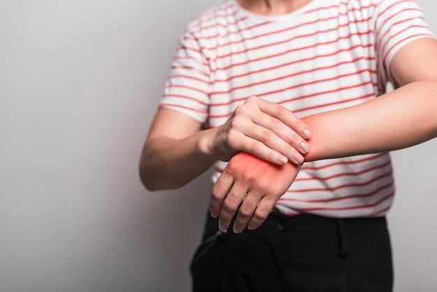 Primo piano della donna che ha dolore in polso contro fondo grigio
