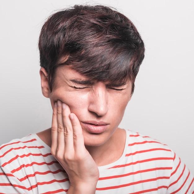 Primo piano della donna che ha mal di denti contro il contesto bianco