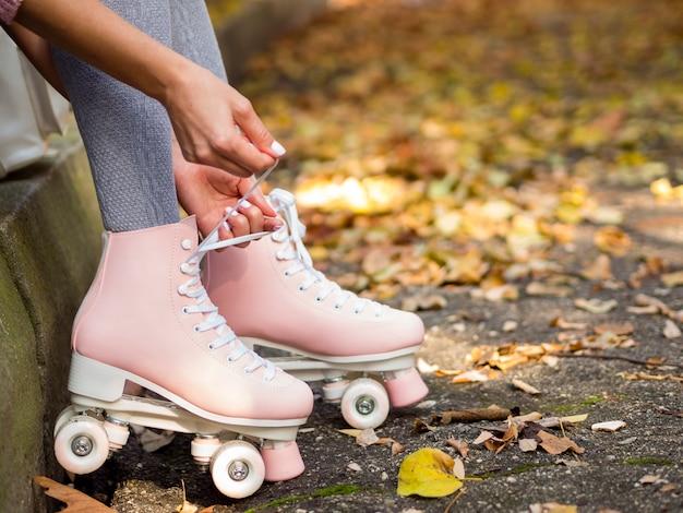 Primo piano della donna che lega i lacci delle scarpe sui pattini di rullo
