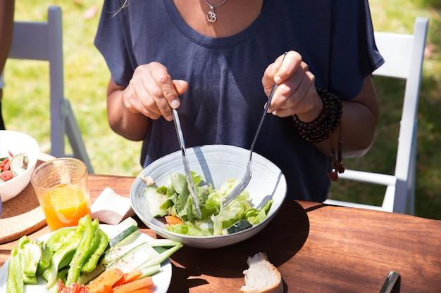 Primo piano della donna che mangia insalata alla tavola all'aperto