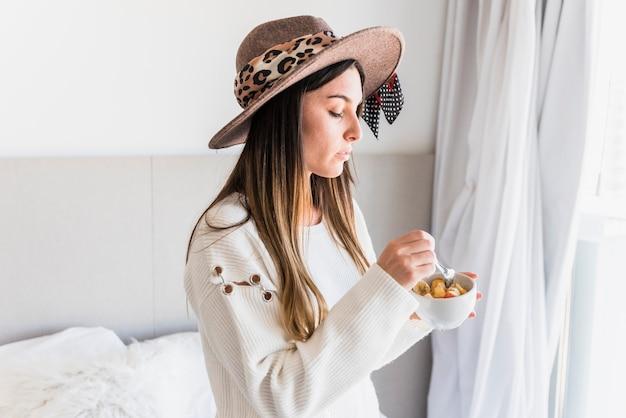 Primo piano della donna che mangia la macedonia nella ciotola bianca