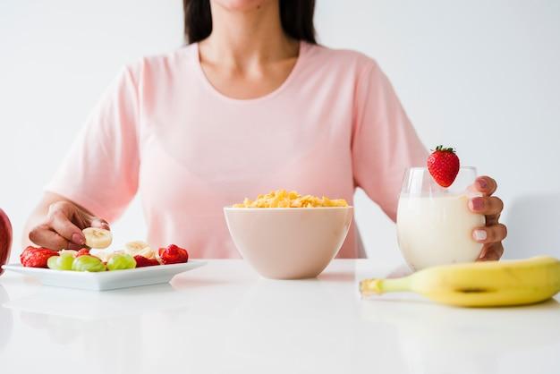 Primo piano della donna che mangia prima colazione sana sullo scrittorio bianco