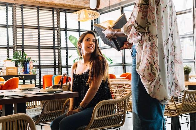 Primo piano della donna che mostra la carta del menu al cliente femminile che si siede nel ristorante