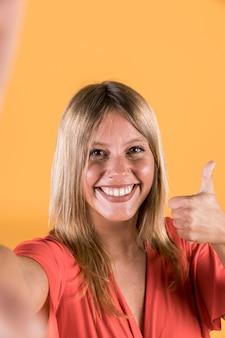 Primo piano della donna che mostra pollice su che esamina macchina fotografica
