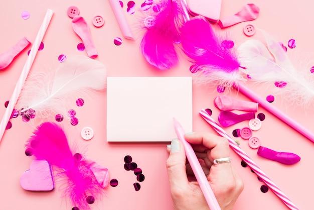 Primo piano della donna che scrive il blocco note con penna e oggetti decorativi su sfondo rosa
