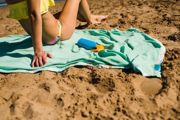 Primo piano della donna che si distende sulla spiaggia sabbiosa