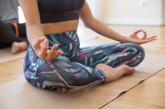 Primo piano della donna che si tiene per mano nel gesto di mudra alla classe di yoga