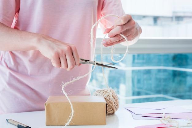 Primo piano della donna che taglia il filo con le forbici sulla tavola di legno