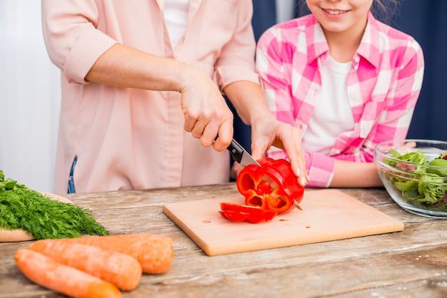 Primo piano della donna che taglia il peperone dolce con il coltello sul tagliere con sua figlia