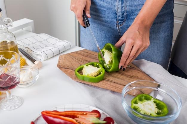 Primo piano della donna che taglia il peperone dolce verde con il coltello sul tagliere sopra lo scrittorio bianco