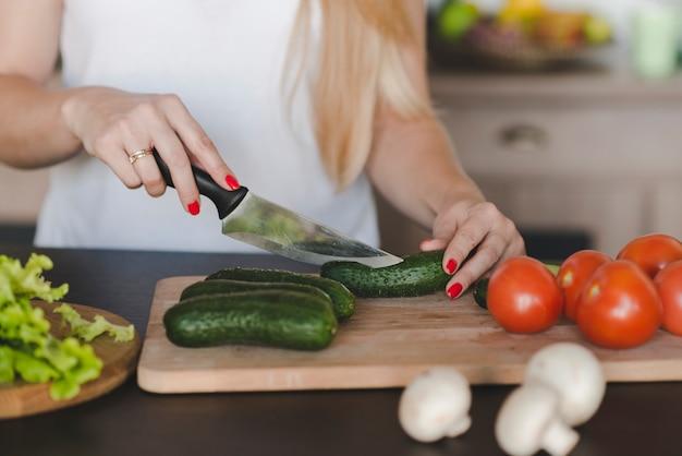 Primo piano della donna che taglia verdura con coltello affilato sul tagliere