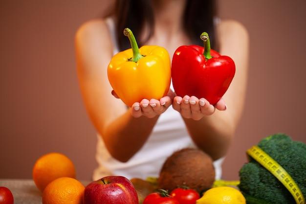 Primo piano della donna che tiene i peperoni gialli e rossi in sue mani