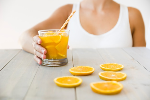 Primo piano della donna che tiene il bicchiere di succo d'arancia con cannuccia sulla tavola di legno