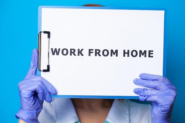 Primo piano della donna che tiene in bianco con il lavoro dell'iscrizione dalla casa che richiede la fermata di diffusione covid-19