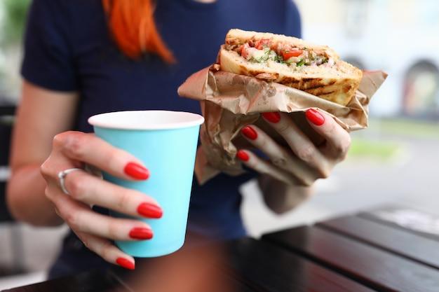 Primo piano della donna che tiene tazza di caffè caldo e delizioso panino. pausa per pranzo veloce. femmina seduta all'aperto sulla piattaforma estiva. gustoso brunch all'aria aperta. concetto di cibo