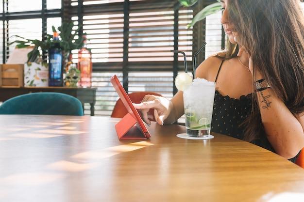Primo piano della donna che tocca la tavoletta digitale con bicchiere da cocktail sulla tavola di legno