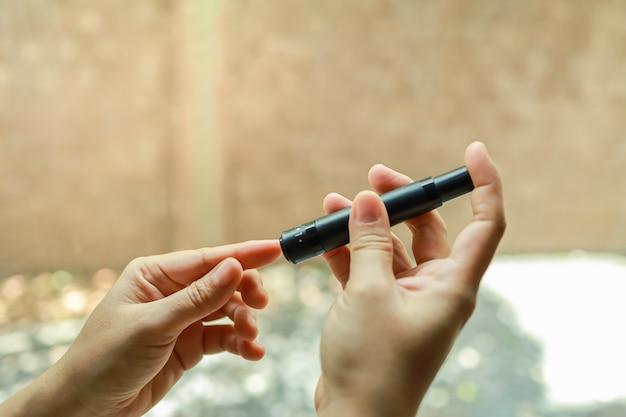 Primo piano della donna che utilizza la lancetta sul dito per controllare il livello di zucchero nel sangue