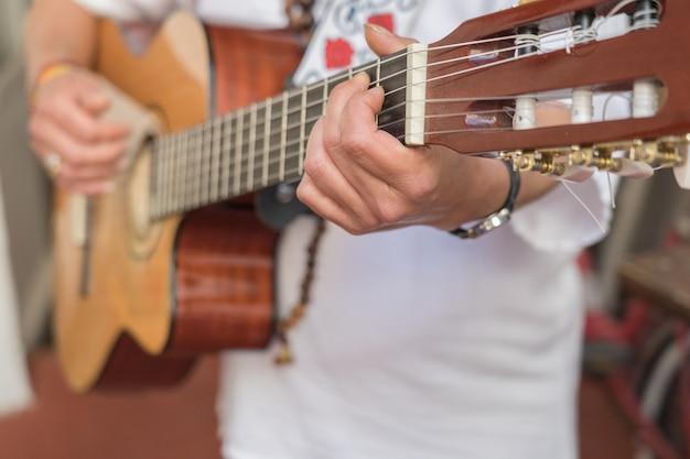 Primo piano della donna cubana che porta vestito cubano tradizionale che gioca una chitarra acustica. preso a l'avana, cuba