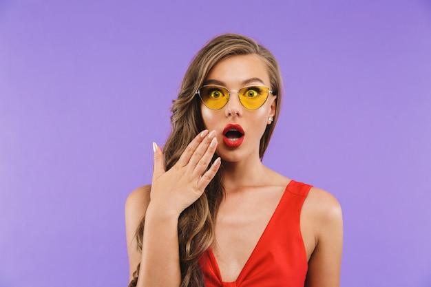Primo piano della donna d'avanguardia che porta vestito rosso e gli occhiali da sole che si chiedono con la bocca aperta