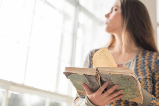 Primo piano della donna della sfuocatura che sta vicino alla finestra che tiene libro d'annata a disposizione