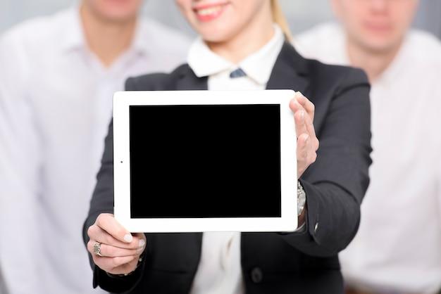 Primo piano della donna di affari che mostra compressa digitale dello schermo in bianco verso la macchina fotografica