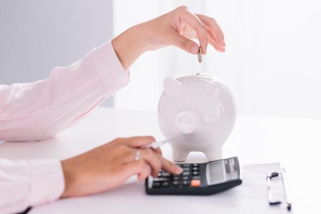 Primo piano della donna di affari che per mezzo del calcolatore che inserisce moneta nel porcellino salvadanaio