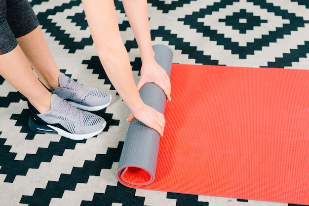 Primo piano della donna di forma fisica che rotola il tappeto rosso di esercizio sul tappeto