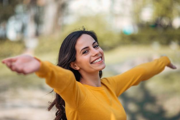 Primo piano della donna felice che sta con a braccia aperte all'aperto, sorridendo alla macchina fotografica.