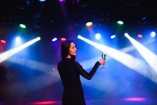 Primo piano della donna felice della corsa mista in vestito paillettes che balla su un partito