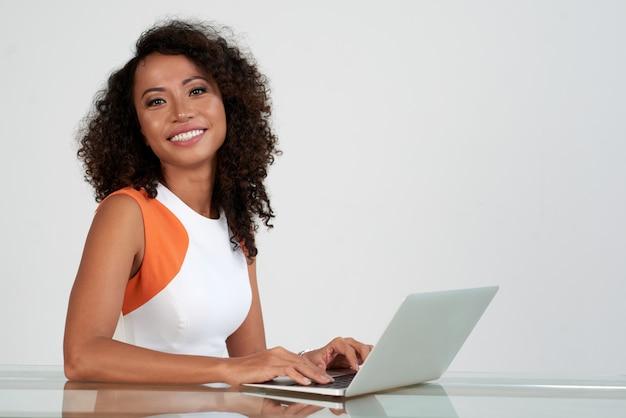 Primo piano della donna graziosa che ditting allo scrittorio con il computer portatile che sorride alla macchina fotografica